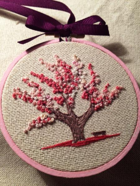 There is a bench under the tree. Pink tree in bloom spring floral design