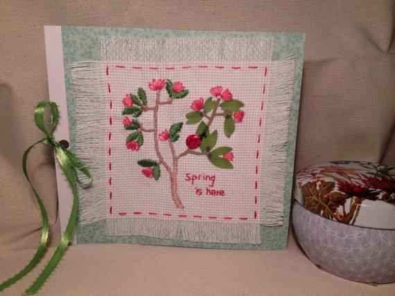 Spring is here floral natural design card. A ladybug in the green leaves and